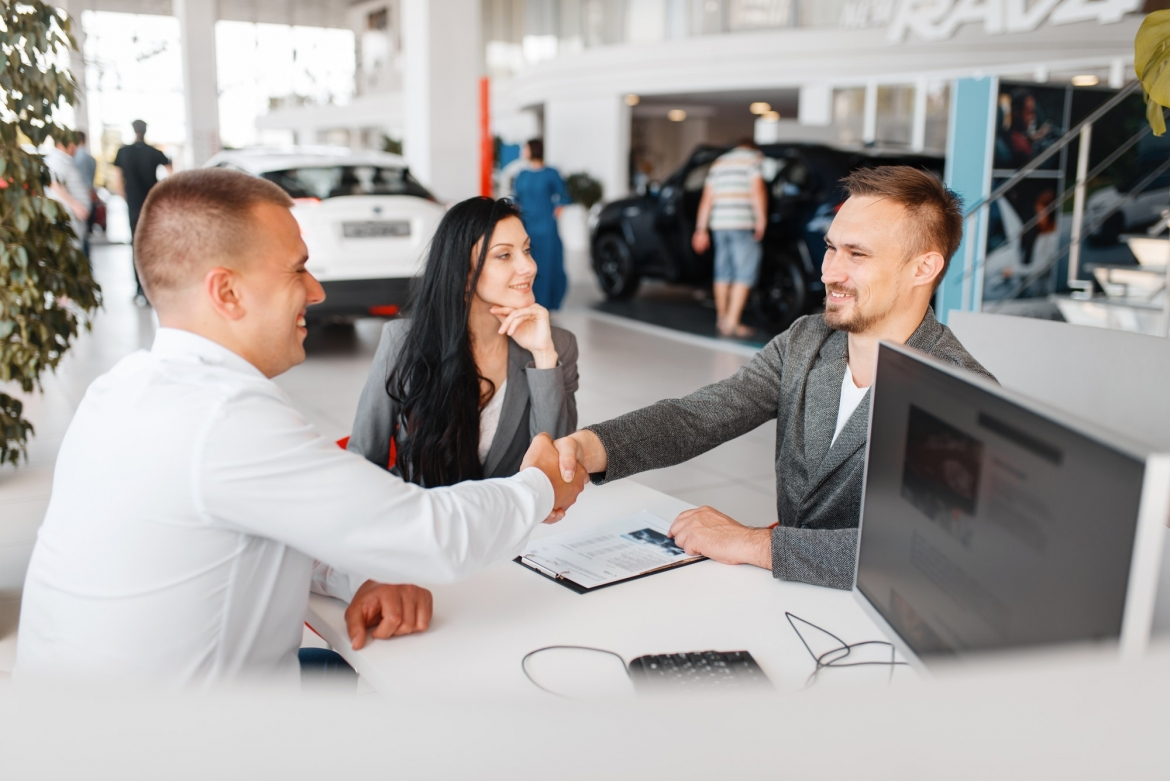 manager-and-couple-make-out-the-sale-of-a-new-car.jpg