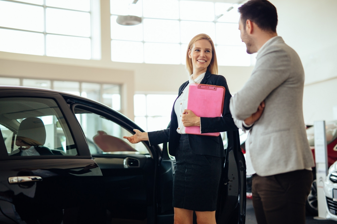 professional-salesperson-selling-cars-at-dealership-to-buyer.jpg