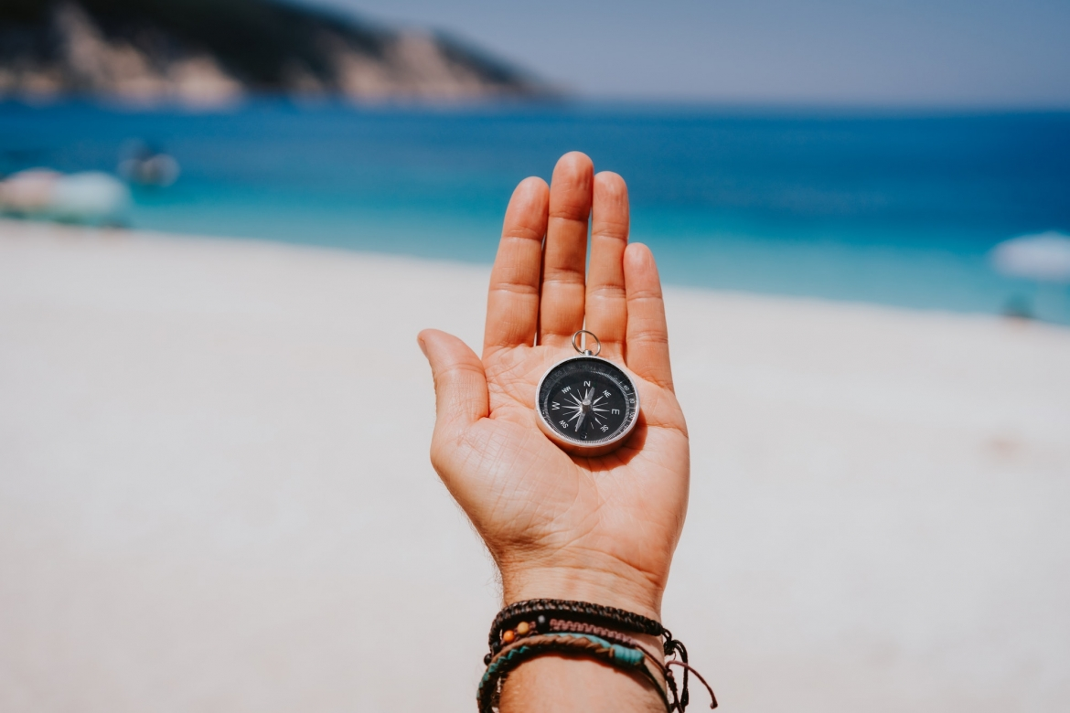 stretched-hand-palm-with-black-metal-compass-against-summer-beach-and-blue-sea-follow-your-way.jpg