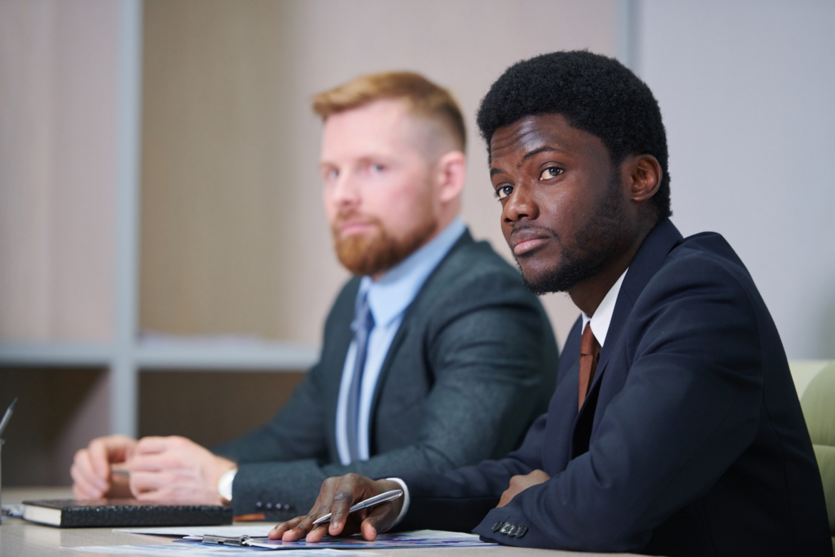 young-african-businessman-in-suit-listening-to-coach.jpg