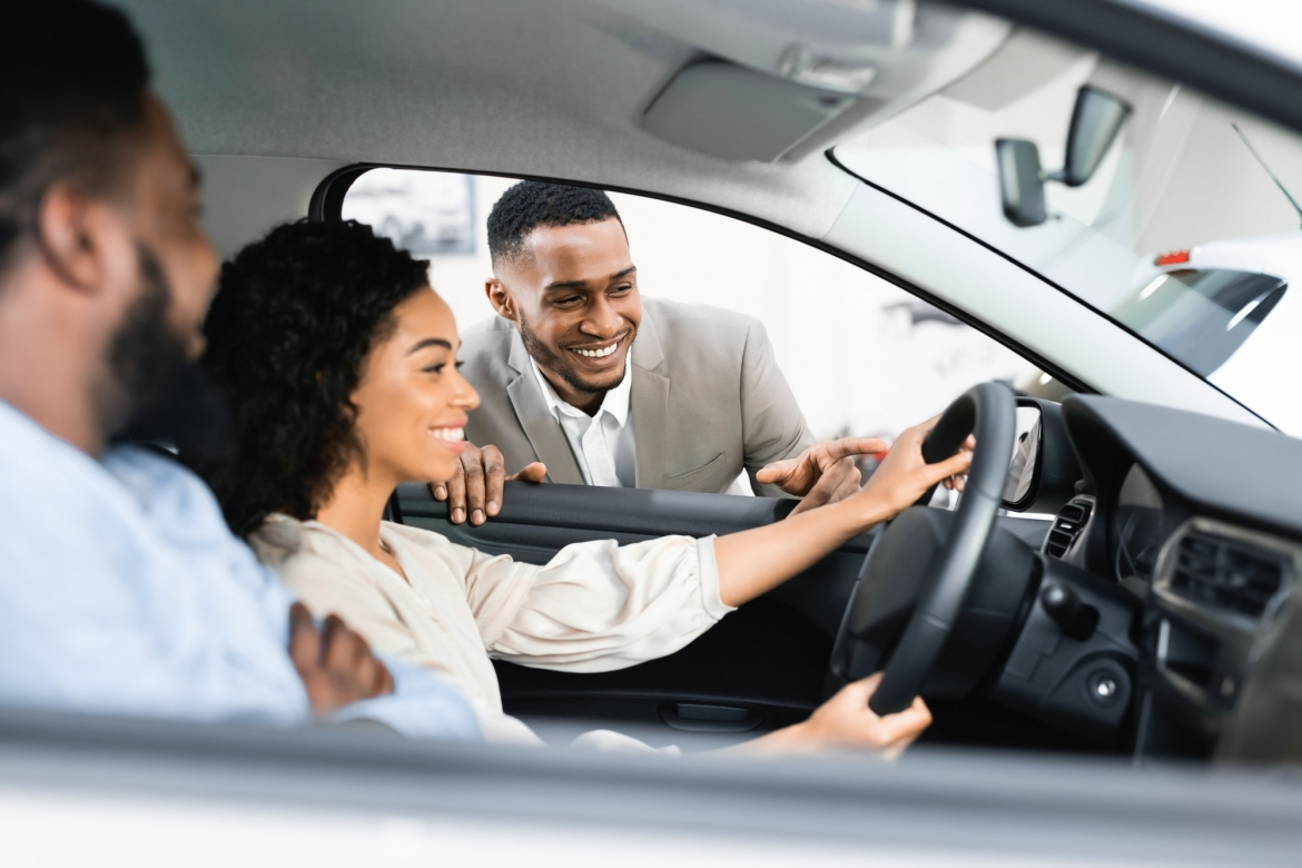 couple-buying-car-testing-it-with-dealer-sitting-in-auto.jpg