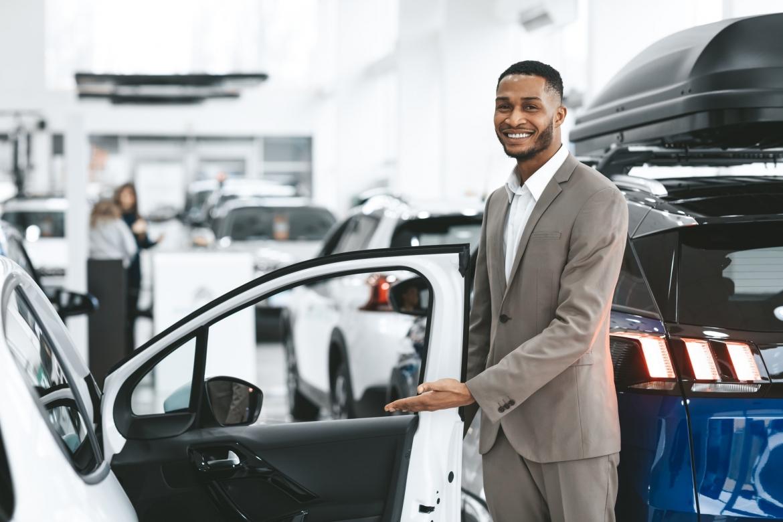 dealer-showing-new-automobile-opening-door-standing-in-dealership-center.jpg