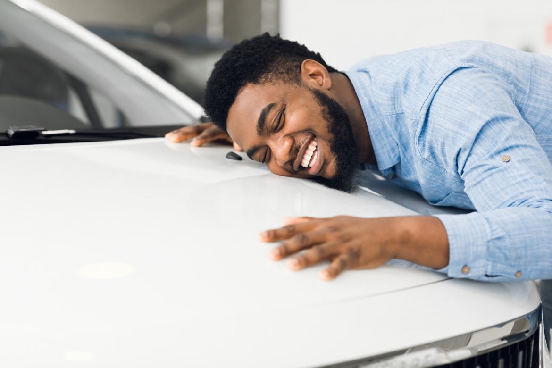 happy-african-american-man-hugging-new-car-in-auto-dealership.jpg